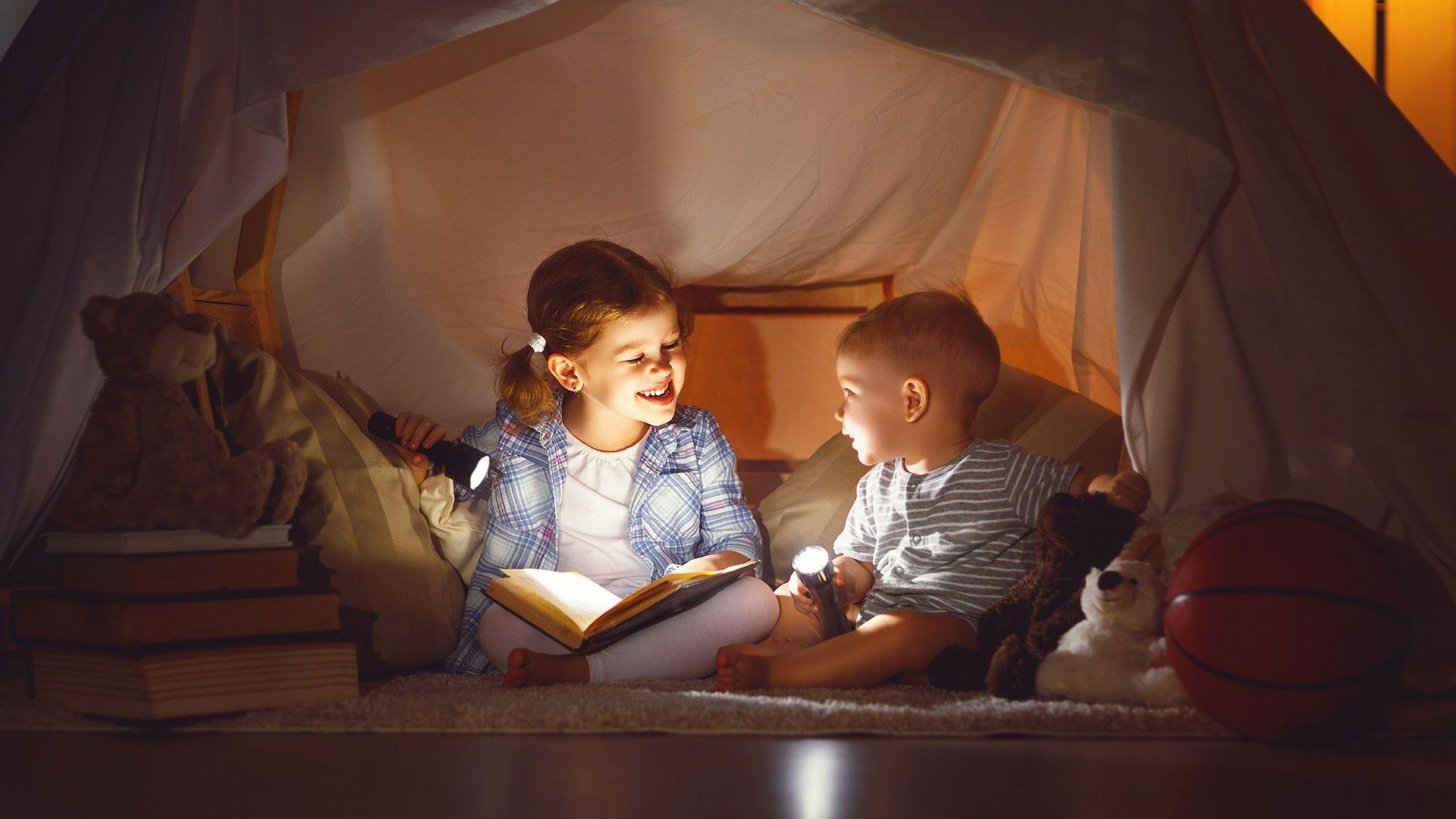 Kinderen spelen in een tent gemaakt van dekens - thuiswerken - kinderactiviteiten